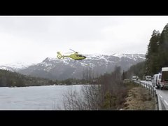 Thumbnail of Helicopter balances on road railing