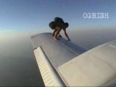 Thumbnail of Skydiver climbs on the wing of a plane