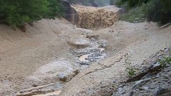 Thumbnail of Massive boulders carried over a dam in a flash flood